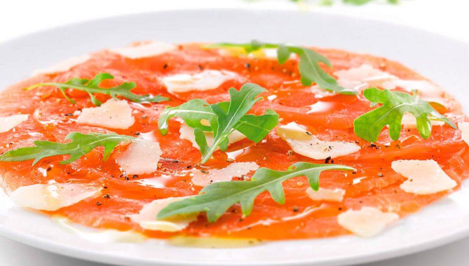preparacion de carpaccio de salmón ahumado con rucula y queso parmesano